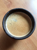 Coffee in a clay cup. Hot coffee in a clay cup on a wooden surface Stock Image