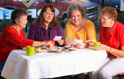 Coffee Club Shares Pictures. 4 older close friends sitting in a cafe having coffee and sweets sharing family pictures.  Shallow depth of field Stock Photo