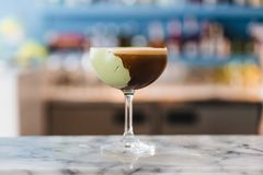 Coffee cocktail with green paste in wine glass on marble top counte. R Stock Photography