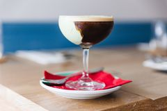 Coffee cocktail with green paste in wine glass on red napkin and plate.  Royalty Free Stock Photography