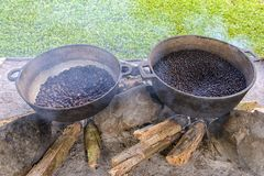 Coffee and cocoa beans roasting in metal basin with Royalty Free Stock Photos