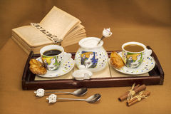 Coffee and coffe-milk table. Coffee and coffee-milk table with sucre, cookies and a book on a brown background Royalty Free Stock Photo