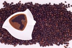 Coffee on coffee beams. Triangular cup with coffee on coffee beams Royalty Free Stock Photo