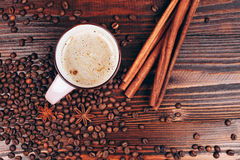 Coffee with coffee beans and cinnamon. Cup of coffee with foam, cinnamon sticks, star anice, coffee beans and place for text, staying on the wooden table Royalty Free Stock Photo