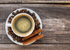 Coffee with coffee beans and cinnamon. Cup of coffee with coffee beans and cinnamon on rustic wooden background. Top view Royalty Free Stock Photography