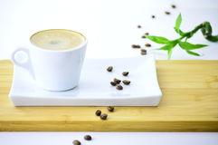 Coffee and coffee beans on a plate. Coffee beans next to a cup of coffee on a plate in white backgraund Royalty Free Stock Image