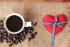 Coffee with coffee beans and red hearts. Royalty Free Stock Image