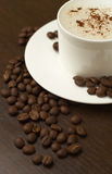 Coffee and coffee beans on the table. Coffee and coffee beans on the brown table Royalty Free Stock Photos