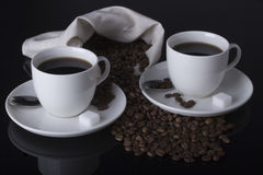 Coffee and coffee beans in table. Two coffee cups and sugar on the mirror Stock Images