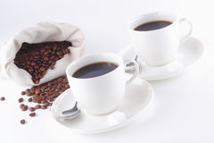 Coffee and coffee beans on the white table. Coffee beans with two cups Stock Photo