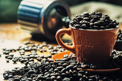 Coffee. Coffee cup full of coffee beans, coffee grinder in the background Royalty Free Stock Photos