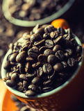 Coffee. Coffee cup full of coffee beans, coffee grinder in the background Royalty Free Stock Photo