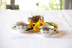 Coffee in coffee cups and a bunch of flowers Royalty Free Stock Photography