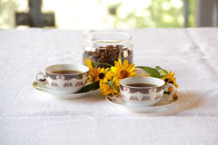 Coffee in coffee cups and a bunch of flowers Royalty Free Stock Photo