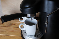 Coffee from the coffee machine is poured into white cups, close-up Royalty Free Stock Image