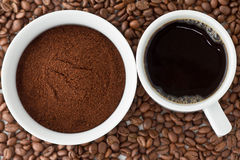 Coffee and coffee powder on top of coffee beans. Coffee powder in bowl and coffee in cup on top of coffee beans royalty free stock photos