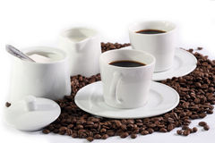 Coffee composition. Two cups of coffee with milk, sugar and coffee grains on the table Stock Images