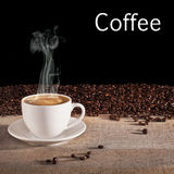 Coffee Concept. A cup of espresso coffee with visible steam rising, on a rustic background with fresh roast coffee beans and space for your own text. Real royalty free stock photo