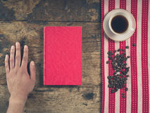 Coffee concept with cup, a male hand and a book Royalty Free Stock Photography