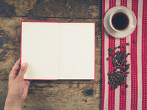 Coffee concept with cup and male hand holding a book Stock Photo