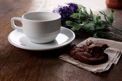 Coffee cookie. Hot coffee and cookie with flower on wood table Royalty Free Stock Images