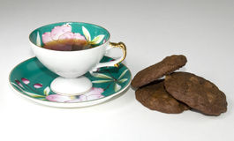 Coffee and cookies. Antique cup with coffee and a few homemade cookies Stock Images