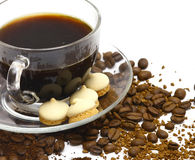 Coffee with cookies. A cup from coffee against coffee grains Royalty Free Stock Photo