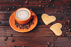 Coffee with cookies. Ceramic orange cup of coffee with foam, with heart shaped cookies and coffee beans, lying on wooden table Stock Photo