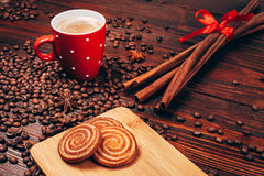 Coffee with cookies and cinnamon. Red cup of coffee with foam, cinnamon sticks, star anice, coffee beans and wooden board with round cookies, staying on the Stock Image