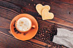 Coffee with cookies and coffee beans. Ceramic orange cup of coffee with foam, with heart shaped cookies and coffee beans, standing on wooden table Stock Image