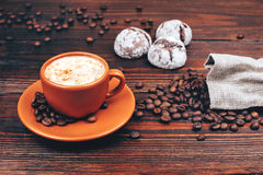Coffee with cookies and coffee beans. Ceramic orange cup of coffee with foam, with cookies and coffee beans, standing on wooden table Stock Images