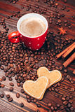 Coffee with cookies. Cup of coffee with foam, cinnamon sticks, star anice, coffee beans and wooden board with heart shaped cookies, staying on the wooden table Royalty Free Stock Photo