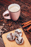 Coffee with cookies. Cup of coffee with foam, cinnamon sticks, star anice, coffee beans and wooden board with threecookies, staying on the wooden table Stock Images