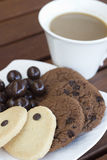 Coffee and Cookies. Cup of coffee and some different cookies in white plate on wooden table royalty free stock images