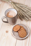 Coffee with cookies. Cup of coffee with cookies and spikelets lying on the wooden table Royalty Free Stock Photos