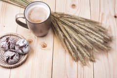 Coffee with cookies. Cup of coffee with cookies and spikelets lying on the wooden table Stock Images
