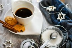 Coffee and cookies. Delicious home made    cinnamon cookies, sugar bowl , warm scarf  mandarin, ,cup of coffee , christmas star  lights, and empty notebook  Lazy Stock Image