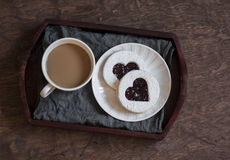 Coffee and cookies-hearts with cranberry jam on a wooden tray. Stock Photos