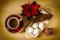 Coffee, cookies, one croissant and a Christmas flower. Enjoying the winter mornings with hot coffee and treats Royalty Free Stock Images