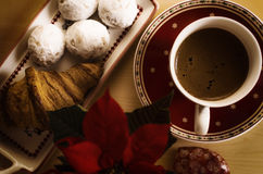 Coffee, cookies, one croissant and a Christmas flower. Enjoying the winter mornings with hot coffee and treats Royalty Free Stock Image