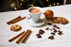 Coffee and snacks on the table on new year table. Coffee and cookies on the  white table on the New Year with garland lights  on background Royalty Free Stock Image