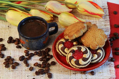 Coffee, cookies and yellow tulips. A cup of coffee and cookies on a saucer, yellow tulips and coffee beans Stock Photo