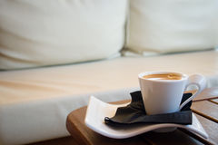 Coffee in cosy cafe. Cosy sofa with coffee cup. Nice warm colors and wooden table for extra comfort Royalty Free Stock Photography