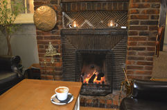 Coffee and a Cosy Fireplace. Nothing beats a cup of coffee sat in front of a roaring log fire in a fireplace, to warm you on a winters evening Royalty Free Stock Images