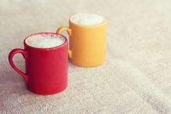 Coffee for a couple with mood. Pair of colored mugs with frothy cappuccino stand on a desk Stock Images