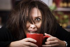 Coffee-Crazed Woman. Half awake woman cradling a mug of coffee Royalty Free Stock Images