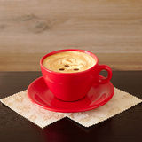 Coffee with cream in a red bowl Royalty Free Stock Photos
