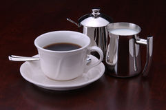 Coffee, Cream and Sugar. A cup of black coffee with a cream pitcher and sugar bowl Royalty Free Stock Images