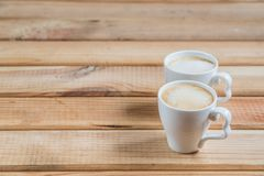 Coffee creamers. two cups of coffee on a wooden table royalty free stock photos