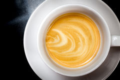 Coffee Crema. Espresso shot patterns in a cappucino cup on a black granite surface royalty free stock photo